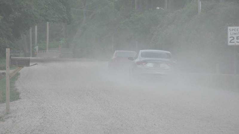 Cars travel down Wall Ave. kicking up dust in Horace, ND.