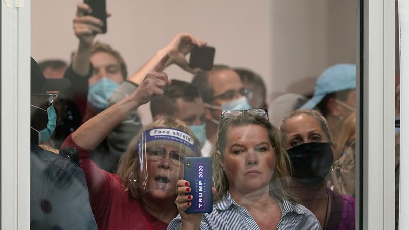 People wanting to be election challengers yell as they look through the windows of the central...