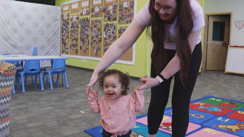 Jillian helps her daughter, Amara, walk across the floor at GiGi's Playhouse in Fargo.