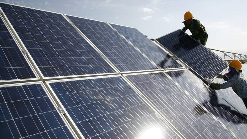 FILE - Workers install solar panels at a photovoltaic power station in Hami in northwestern...
