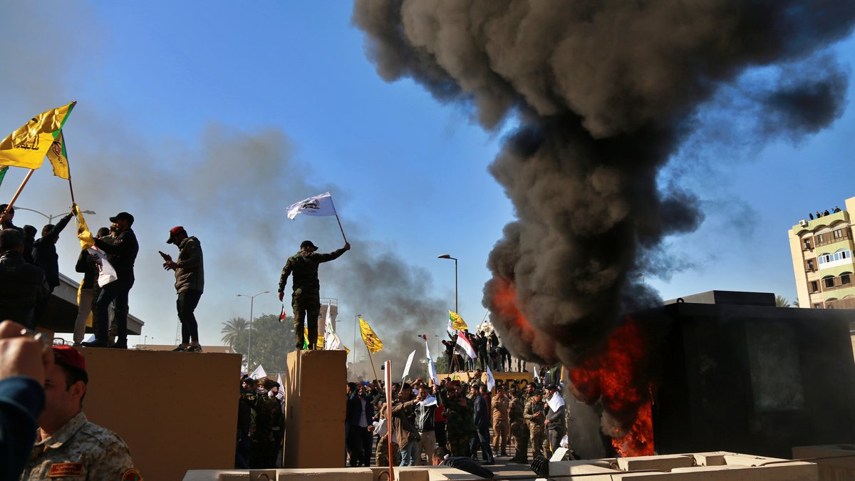 Protesters burn property in front of the U.S. embassy compound, in Baghdad, Iraq, Tuesday,...
