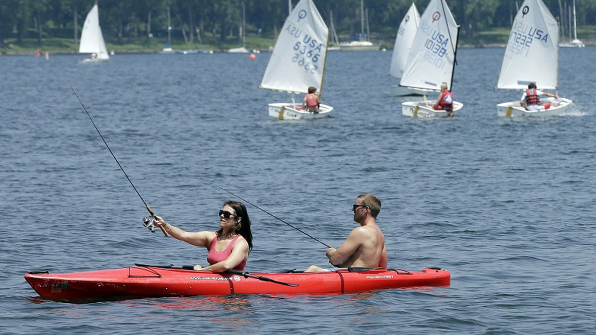 Kayakers try their luck at fishing as sailing enthusiasts navigate the waters of Lake Calhoun, Thursday, July 11, 2013, in Minneapolis. (AP Photo/Jim Mone)