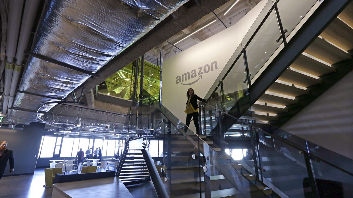 In this Sept. 27, 2017, file photo, an Amazon worker walks down steps in a company office...