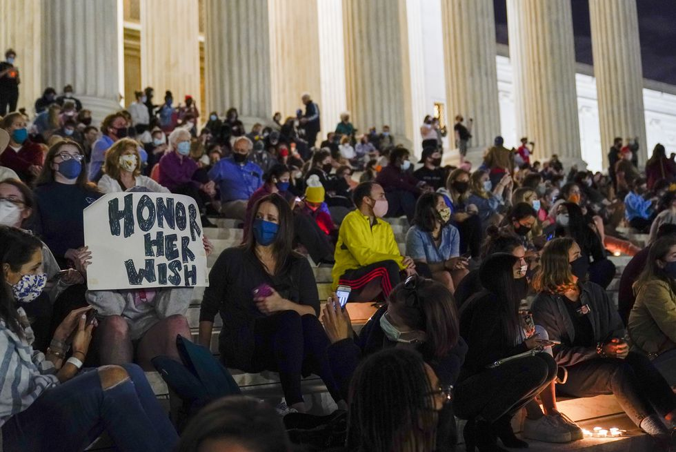 People gather at the Supreme Court Friday, Sept. 18, 2020, in Washington, after the Supreme Court announced that Supreme Court Justice Ruth Bader Ginsburg has died of metastatic pancreatic cancer at age 87.