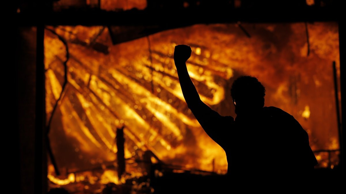 A protester gestures in front of the burning 3rd Precinct building of the Minneapolis Police...