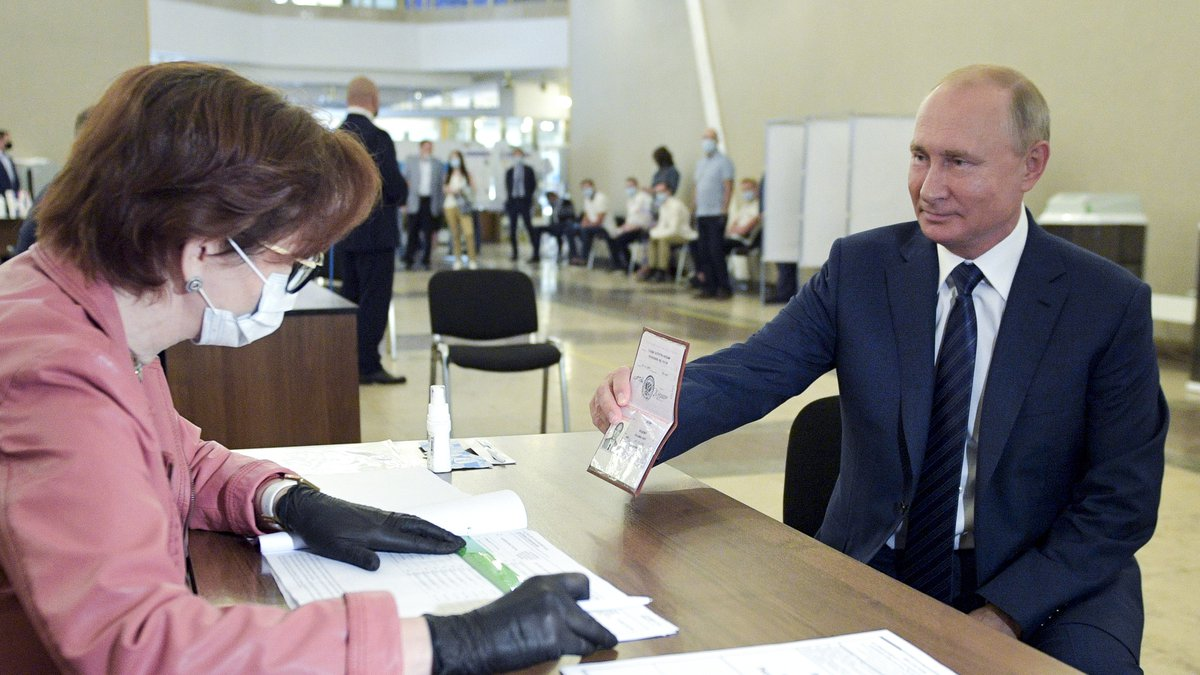 Russian President Vladimir Putin shows his passport to a member of an election commission as he...