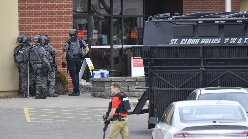 Officers stand near an entrance to the Wells Fargo branch Thursday May 6, 2021, in south St....