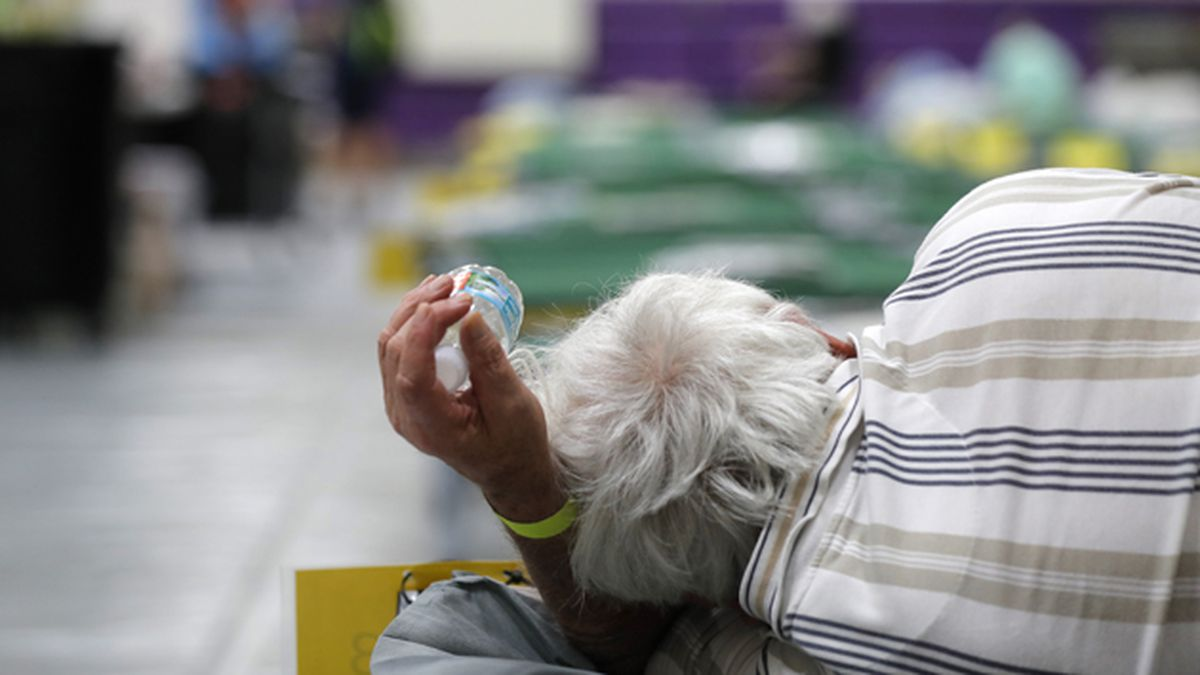 An evacuee lies on a cot at an evacuation shelter for people with special needs, in preparation for Hurricane Dorian, at Dr. David L. Anderson Middle School in Stuart, Fla., Sunday, Sept. 1, 2019. (AP Photo/Gerald Herbert)