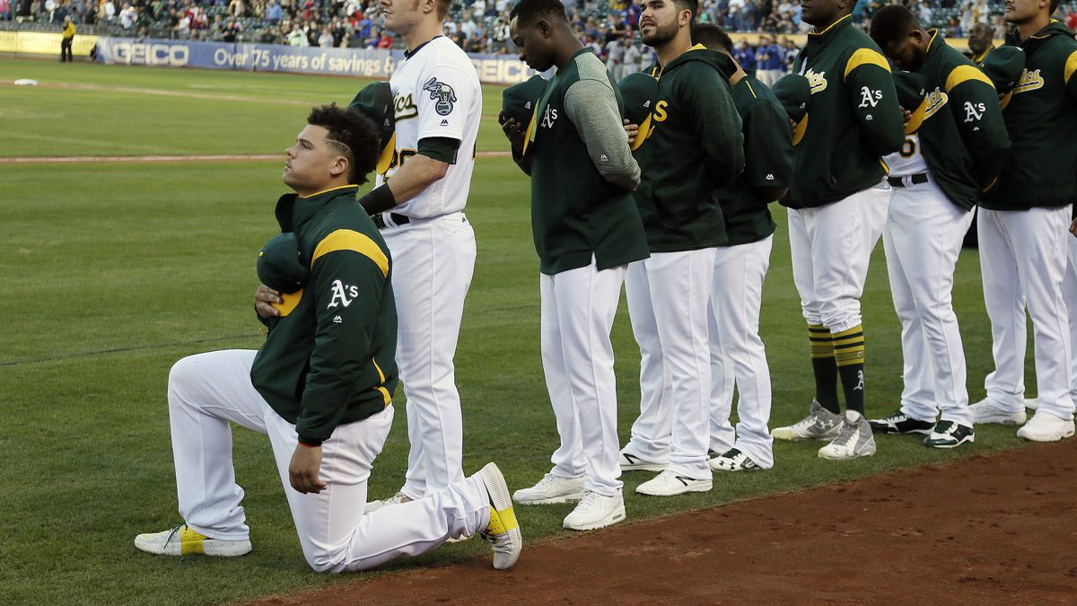 FILE - In this Sept. 23, 2017, file photo, Oakland Athletics catcher Bruce Maxwell kneels during the national anthem before the start of a baseball game against the Texas Rangers in Oakland, Calif. The New York Mets have agreed to a minor league contract with Maxwell, the first major league player to kneel during the national anthem to protest racial injustice in 2017, according to a person familiar with the deal.