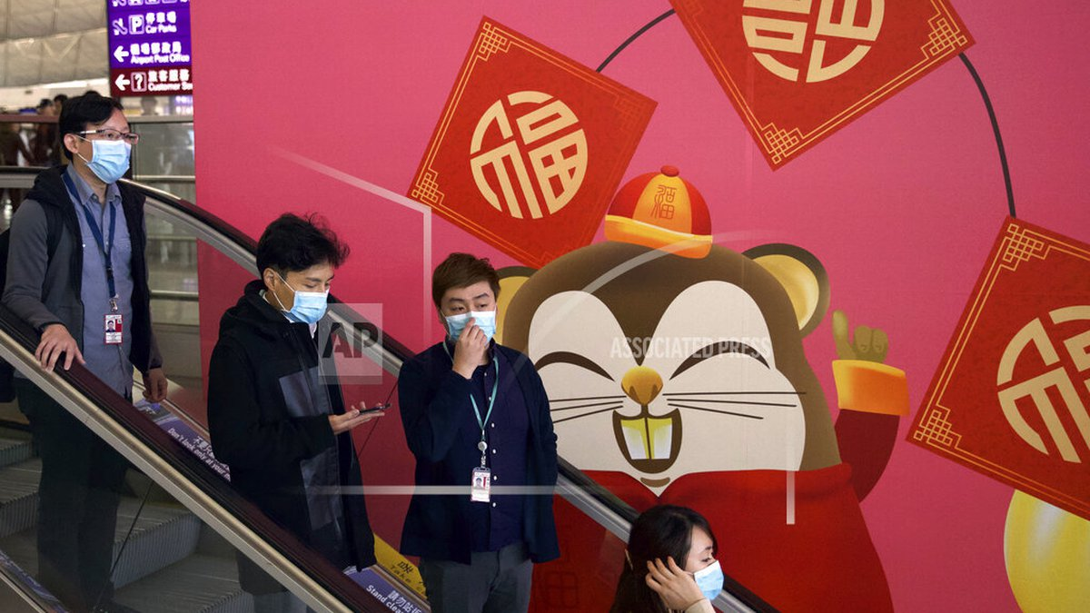 People wear face masks as they ride an escalator at the Hong Kong International Airport in Hong...