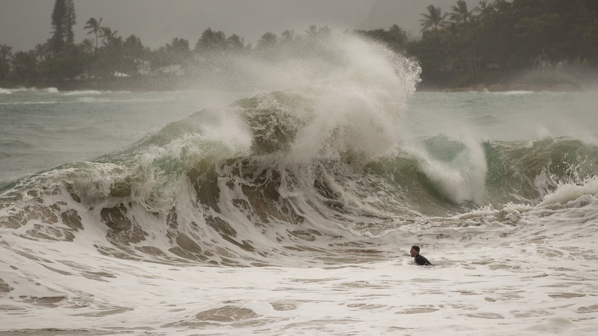 A body surfer prepares to dive under a large wave generated by Hurricane Douglas, at Laie Beach...