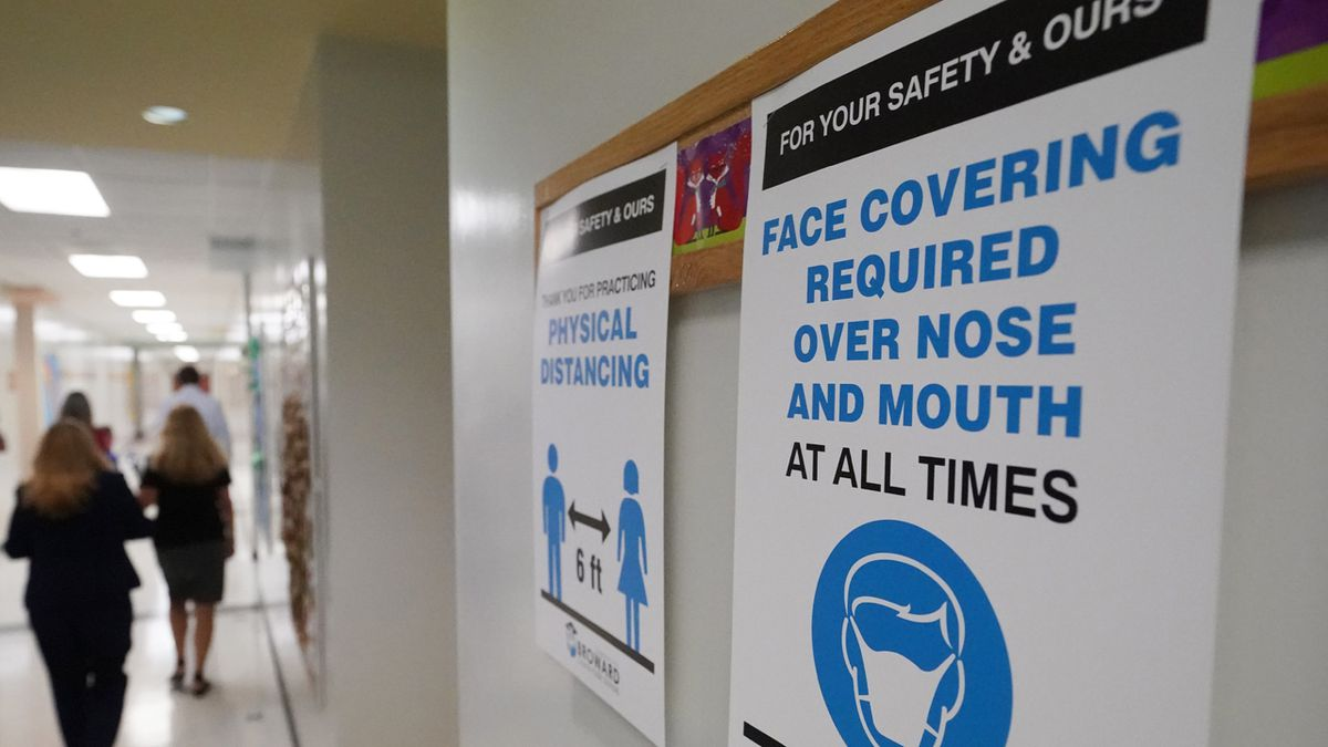 Signs in a hallway reminds students to wear masks and distance themselves at Fox Trail...